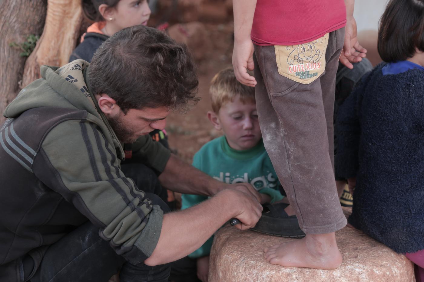 بالصور: رجل سوري يصنع أحذية من الإطارات للأطفال النازحين